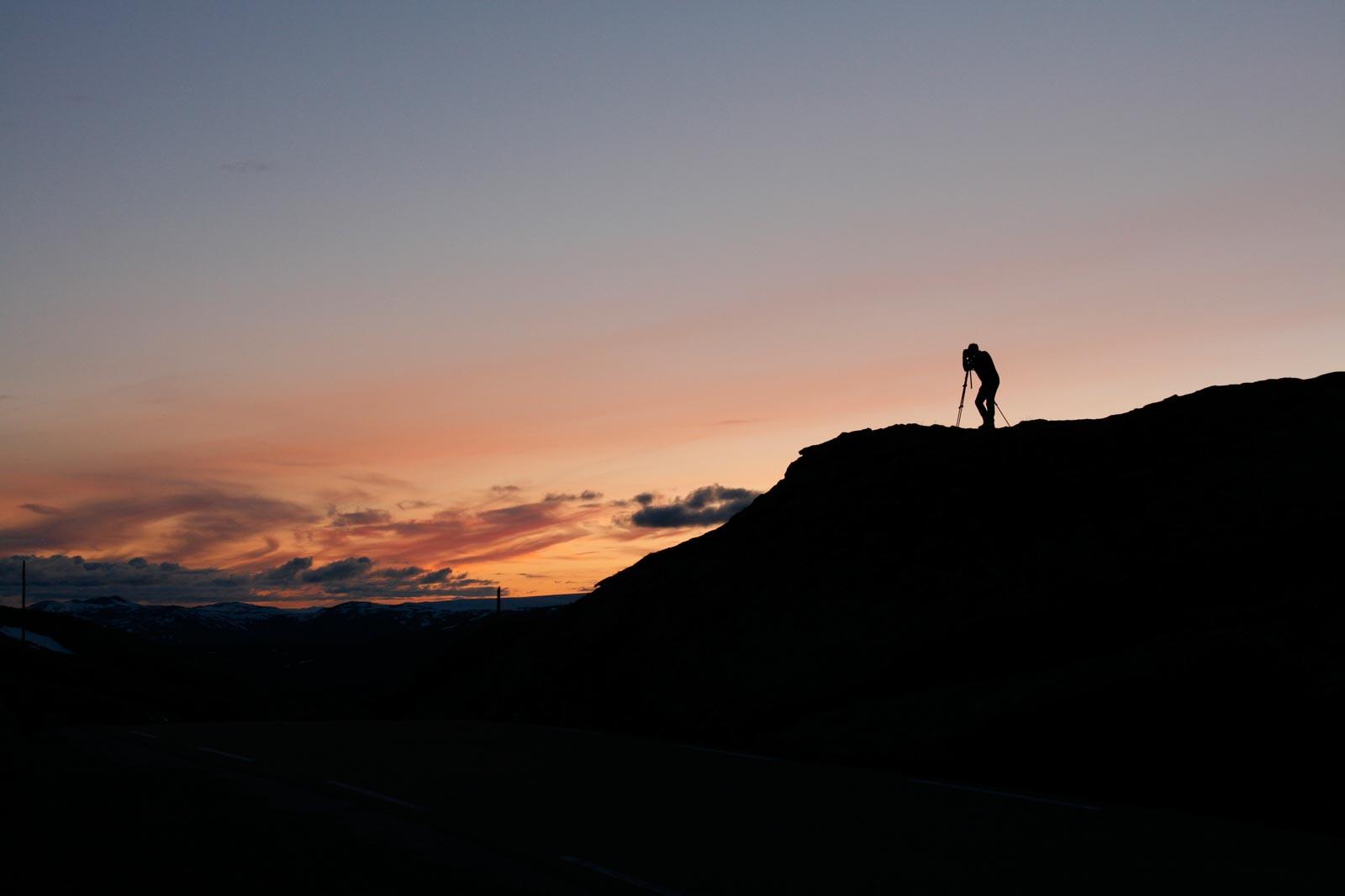 Fotograaf met statief bij een zonsondergang